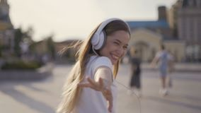 Air kiss. funny girl walking in the city, early morning. woman in big headphones blowing kisses 4K