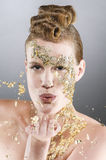 Air kiss with gold. Portrait of a young woman with a make-up of fine gold leaf. She makes a kiss with gold dust into the camera Stock Image