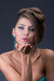 Air kiss from Woman wearing shiny blue earring Stock Photo