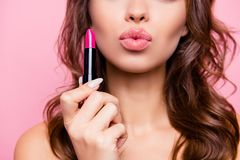 Air kiss for you. Close up cropped shot of femenine gorgeous cha. Rming adorable lady with amazing wavy hair do, tube of hard pink pomade in arm. Pampering, lips Stock Image