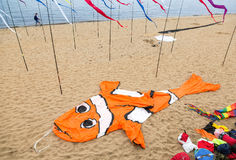 An air kite in the form of a big orange fish lies on a sandy bea Royalty Free Stock Photos