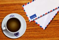 Air mail envelope and coffee cup Royalty Free Stock Image