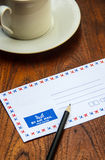 Air mail envelope with pencil and coffee cup Stock Photos