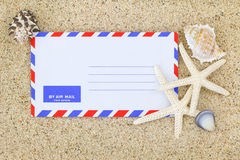 Air mail envelope on the sand decorated with sea shells and Star Stock Images