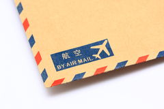 By Air Mail. Air Mail label (in English and Chinese) on a brown air mail envelope Stock Photos