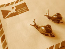 Air mail or snail mail?. Two snails on a South African airmail envelope royalty free stock photo