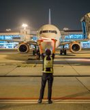 Air Marshaller in motion blur showing sign to tell captain to stop, night time. A manMarshaller showing sign to tell captain on commercial airplane to stop at Stock Photography