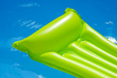 Air mattress is floating in a swimming pool. Green air mattress is floating in blue water of a swimming pool. inflatable  is only partly shown Royalty Free Stock Photos