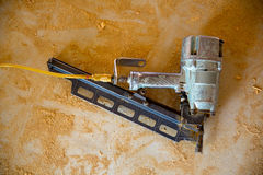 Air nail gun pneumatic framing nailer sawdust floor Royalty Free Stock Image