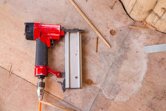 Air Nail Gun on the wooden floor Stock Photos