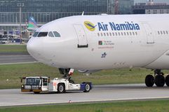 Air Namibia. Close-up of an Air Namibia Airbus A340-300 being towed towards the extended stay ramp, with Frankfurt's Terminal 2 on the background Stock Photo