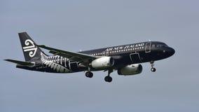 Air New Zealand Airbus A320 em toda a aterrissagem da libré dos pretos no aeroporto internacional de Auckland Fotografia de Stock