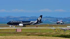 Air New Zealand Airbus A320 en special que toda la librea de los negros el carreteo como rival Jetstar Airbus A320 aterriza en el Foto de archivo libre de regalías