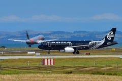Air New Zealand Airbus A320 en special que toda la librea de los negros el carreteo como rival Jetstar Airbus A320 aterriza en el Foto de archivo