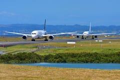 Air New Zealand Boeing 787-9 Dreamliner och dess chartrade Hög-fluga flygbuss A330 som åker taxi på Auckland den internationella  Arkivfoto