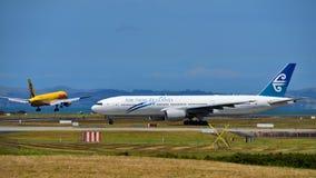 Air New Zealand Boeing 777-200ER que taxiing como linhas aéreas Boeing da carga de DHL Tasman 757 terras do cargueiro Fotografia de Stock