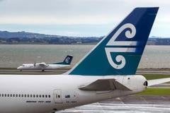 Air New Zealand Boeing 747-419 ZK-NBT en la pista de despeque en el aeropuerto internacional de Auckland con una rociada 8 de Air imagen de archivo
