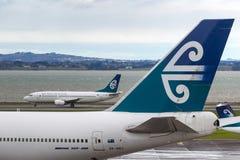 Air New Zealand Boeing 747-419 ZK-NBT sur le macadam à l'aéroport international d'Auckland avec Air New Zealand Boeing 737 derriè Photo libre de droits