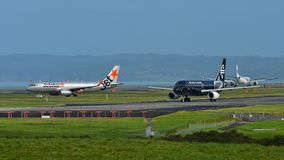 Air New Zealand e Jetstar Airways Airbus A320 que taxiing para a partida no aeroporto internacional de Auckland Imagens de Stock