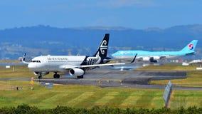 Air New Zealand flygbuss A320 som åker taxi med Korean Air Boeing 747-8i i bakgrunden på Auckland den internationella flygplatsen Royaltyfri Fotografi