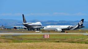 Air New Zealand flygbuss A320 som åker taxi, medan den Singapore Airlines Boeing 747-400 fraktbåten tar av på Auckland den intern arkivbilder