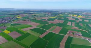 Air panoramas of agricultural fields and wind generators producing electricity. Alternative energy, three wind turbines. Air panoramas of agricultural fields and stock video