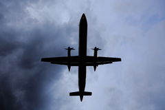 Air Plane in Dark Sky. Silhouetted prop air plane against a foreboding cloudy sky stock images