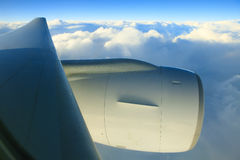 Air plane engine and wing floating over white cloud and blue sky Royalty Free Stock Image