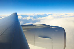 Air plane engine and wing floating over white cloud and blue sky Royalty Free Stock Photography
