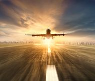 Air plane flying over airport runway with city scape and sunset Stock Photos