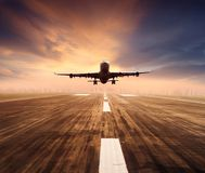 Air plane flying over airport runway with city scape and sunset sky background royalty free stock photo