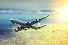 Air plane flying over cloud scape and sun light behind Stock Image