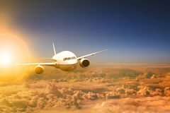 Air plane flying over cloud scape and sun light behind Royalty Free Stock Image