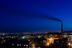 Air pollution. Tall smokestack belches smoke into sky over night city, copy space Stock Photos