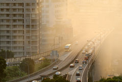 Air pollution. Scenic with cars on highway and yellow smoke in city Royalty Free Stock Photography