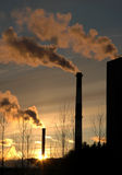 Air Pollution. Pollution spewing into the air from industrial chimneys, at sunset Stock Photos