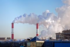 Air pollution in the city. Smoke from the chimney on blue sky background Royalty Free Stock Photos