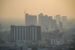 Air pollution in the city. Bangkok Thailand Center and modern skyscraper city in misty gold lighting sunset air pollution in the city behind pollution haze stock photography