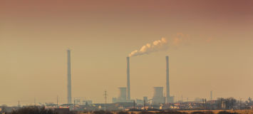 Air pollution from coal-powered plant smoke stacks. And industrial cityscape, profiled on sunset colors Stock Image