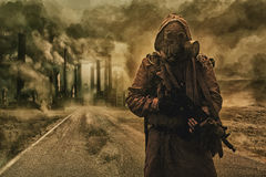 Air pollution concept. Post-apocalyptic air pollution. Survivor in tatters and gas mask on the background of pipes on abandoned road. Nature protection concept Stock Image