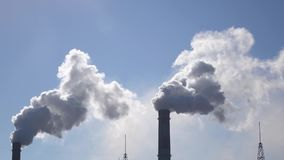 Air pollution from industrial chimneys spew clouds smoke in sky. Two working pipes in plant from which steam comes out, industrial factory, near low buildings stock video