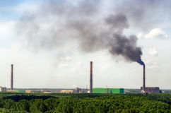 Air pollution from industry. Factory chimney emitting black smoke into the air Royalty Free Stock Photo