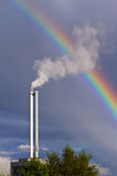 Air pollution and rainbow. Pollution spewing into the air from industrial chimney, with a rainbow in the background Royalty Free Stock Photo