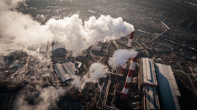 Air pollution by smoke coming out of two factory chimneys. Aerial view Royalty Free Stock Images
