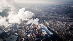 Air pollution by smoke coming out of two factory chimneys. Aerial view Royalty Free Stock Photography