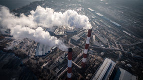 Air pollution by smoke coming out of two factory chimneys. Aerial view Stock Photos