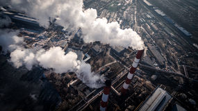 Air pollution by smoke coming out of two factory chimneys. Aerial view Royalty Free Stock Photos