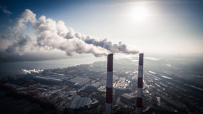 Air pollution by smoke coming out of two factory chimneys. Aerial view Stock Images