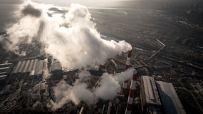 Air pollution by smoke coming out of two factory chimneys. Aerial view Stock Photo
