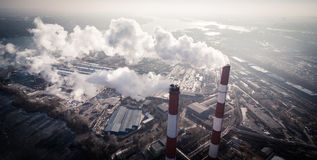 Air pollution by smoke coming out of two factory chimneys. Aerial view Stock Image